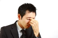 Japanese businessman suffer from a eyestrain  Royalty Free Stock Photography