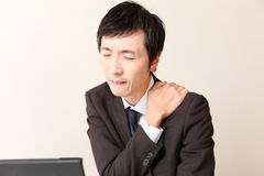 Japanese businessman suffers from neck ache Stock Images