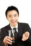 Japanese Businessman takes supplement  Royalty Free Stock Photography