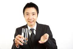Japanese Businessman takes supplement  Royalty Free Stock Images