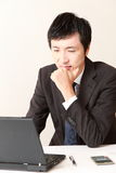 Japanese businessman worries about something Royalty Free Stock Photo