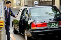 Japanese businessmen call a taxi to work in the morning Stock Images