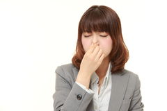 Japanese businesswoman holding her nose because of a bad smell. Studio shot of young Japanese businesswoman on white background stock photo