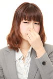 Japanese businesswoman holding her nose because of a bad smell. Studio shot of young Japanese businesswoman on white background royalty free stock images