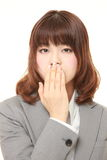 Japanese businesswoman making the speak no evil gesture. Studio shot of young Japanese businesswoman on white background royalty free stock images