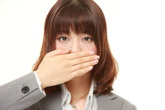 Japanese businesswoman making the speak no evil gesture. Studio shot of young Japanese businesswoman on white background stock photos
