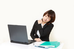 Japanese businesswoman suffers from neck ache Royalty Free Stock Image