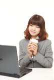 Japanese businesswoman takes a coffee break Royalty Free Stock Photography