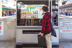 Japanese buy a drink from an automatic vending machine Royalty Free Stock Image