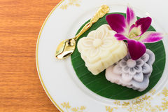 Japanese Cake with Golden Spoon and Orchid. Two Japanese Cakes Placed on Banana Leaf with Golden Spoon and an Orchid Flower Royalty Free Stock Images