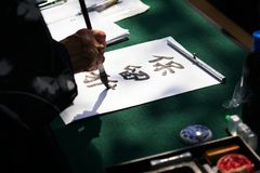 Japanese calligraphy with ink brush on paper. Japanese calligraphy, unrecognizable person writing kanji characters with ink brush on paper, english translation Stock Images