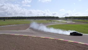 Aerial view car drifting with smoke from burning tires on speed track