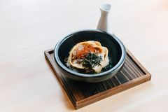 Japanese Chashu Don: Steam Rice topping with Roasted Pork Belly, Yolk, Dried Seaweed and Saffron. Served in black ceramic bowl. Japanese Chashu Don: Steam Rice stock photos