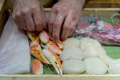 Japanese Chef cooking sashimi food. Steamed giant crabs, shell, fish raw prepare to make sushi in Japanese food. Select focus at hand of chef Stock Photos