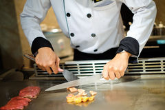 Japanese chef deliberately preparing and cooking traditional beef teppanyaki Royalty Free Stock Photo