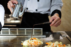 Japanese chef deliberately preparing and cooking traditional beef teppanyaki. On a hot plate Royalty Free Stock Photo