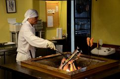 Japanese chef in kitchen grills fish on indoor coal fire Stock Photography