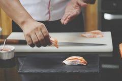 Japanese chef making salmon sushi Stock Image