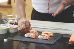 Japanese chef making salmon sushi Stock Images