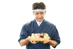 Japanese chef with a plate of sushi Royalty Free Stock Image