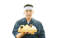 Japanese chef with a plate of sushi Stock Images