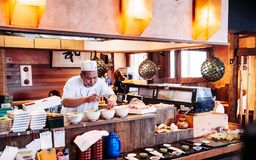 Japanese chef preparing sashimi rice bowl in local small Japanese restaurant stock image