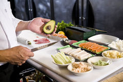 Japanese chef in restaurant with sushi ingredients. Japanese chef in restaurant with fresh ingredients for making sushi rolls Royalty Free Stock Photo