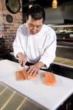 Japanese chef slicing raw fish for sushi. Japanese chef in restaurant slicing raw fish for salmon sushi Royalty Free Stock Photo