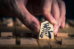 Japanese chess and hands Stock Image