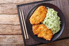 Japanese chicken cutlets in breadcrumbs Panko and noodles with g Royalty Free Stock Photos