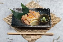 Japanese chicken grilled with sea salt served with sliced lemon and wasabi in stone rectangle plate with chopstick on makisu. Royalty Free Stock Image