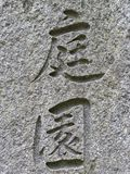 Japanese / Chinese letters signifying `Garden` engraved on stone wall. Close-up of Japanese or Chinese letters on textured gray stone wall royalty free stock photo