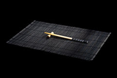 Japanese chopsticks on bamboo mat. On black background Royalty Free Stock Photo