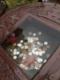 Japanese coins in little stone basin of a shrine. Stock Photos