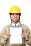 Japanese construction worker with clip board. Studio shot of young Japanese man on white background Stock Photo