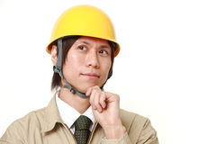 Japanese construction worker thinks about something. Studio shot of young Japanese man on white background royalty free stock image