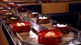 Japanese conveyor belt restaurant - bowls with food moving past the tables stock video