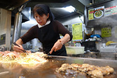 Japanese cook prepares the famous okonomiyaki for the guests in Stock Photos