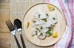 Japanese Cooked fish fillet piece with lemon and spices on wooden tray on dining table - pangasius dolly fish meat royalty free stock image