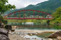 Japanese countryside landscape with bright red bridge over Kiso. River. Kiso valley, Nagano, Japan royalty free stock images