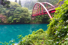 Japanese countryside with view of red arch bridge and vivid blue. Lake in the forest. Shima, Japan Stock Images