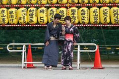 Japanese couple at Mitama matsuri, Yasukuni shrine in Tokyo, Japan. Traditional or modern? Japanese men and woman in traditional kimono with camera looking at stock images