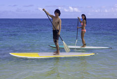 Japanese couple on paddle boards Stock Images