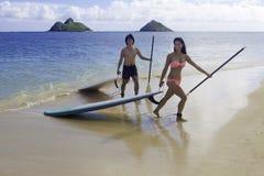 Japanese couple on paddle boards Royalty Free Stock Image