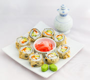 Japanese cuisine-Deep fried sushi roll. Deep fried sushi roll placed in a circle with ginger in the middle, wasabi on the side and a bottle of soy sauces in the Stock Photo