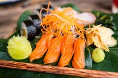 Japanese cuisine sushi and sashimi. Japanese cuisine delicious sushi rolls and fresh sashimi served on a green leaf at restaurant Royalty Free Stock Photos