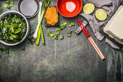 Japanese cuisine ingredients for tasty cooking: wakame seaweed, Silken tofu, spring onions and Miso paste on aged background, top Royalty Free Stock Photos