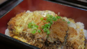 Japanese cuisine Katsudon. Fried pork with egg, onion on rice stock video footage