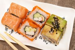 Japanese cuisine. Sushi rolls on white plate, wooden background.  royalty free stock photos