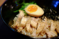 Japanese cuisine rice with soft boil eggs. And fried pork topped white sesame stock photography